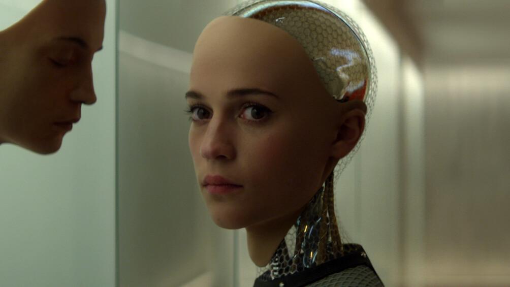 Die Roboterfrau Ava blickt in die Kamera, vor ihr an der Wand befindet sich eine Maske.