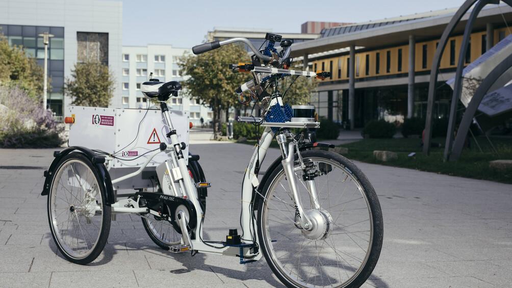 Ein modernes, weißes Lastenrad steht im Zentrum des Bildes.
