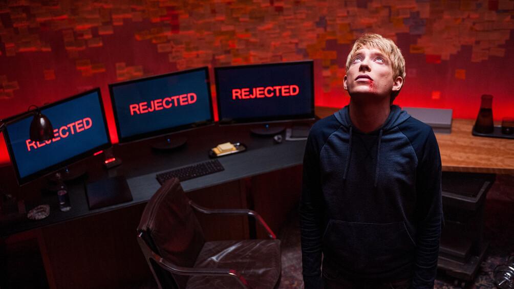 """Caleb steht vor einer Reihe von Bildschirmen, auf denen in roten Buchstaben """"Rejected"""" steht. Er blickt nach oben."""