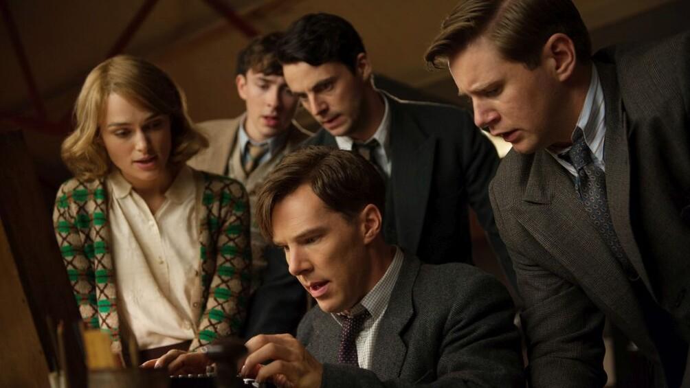 Alan Turing, Joan Clarke und andere Wissenschaftler stehen gespannt um die Maschine Enigma herum.