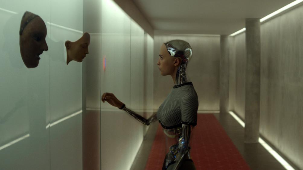 Die Roboterfrau Ava steht im Zentrum des Bildes in einem langen Flur. An der rechten Wandseite hängen Masken, Ava blickt eine der Masken an.