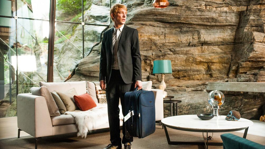 Caleb steht mit einem blauen Koffer in einem modern eingerichteten Wohnzimmer.