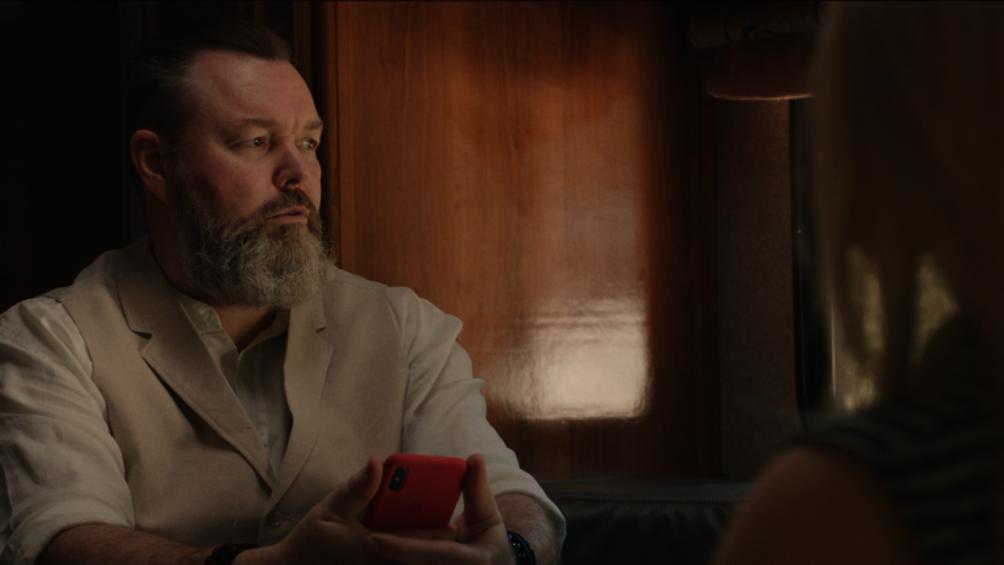 Der Protagonist des Films, Chuck, sitzt in seinem Wohnmobil mit seinem Handy in der Hand, im gegenüber sitzt die Roboterfrau Harmony.