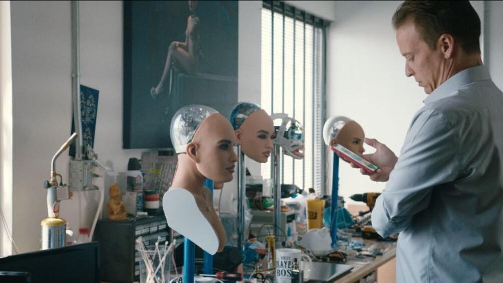 Ein Mann steht vor verschiedenen Köpfen des Roboters Harmonie, er hält ein Handy in der Hand.