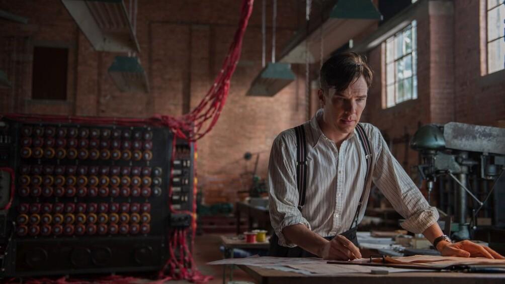 Der Wissenschaftler Alan Turing steht im Vordergrund, vor ihm auf dem Tisch befinden sich Pläne, im Hintergrund sieht man eine große Maschine.