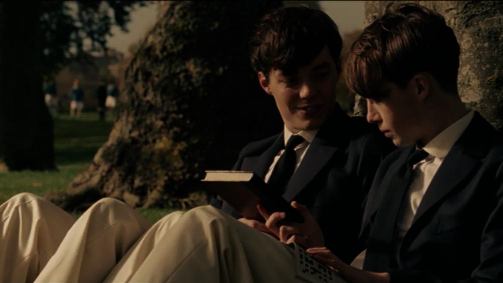 Der junge Alan Turing sitzt neben seinem Jugendfreund Christopher unter einem Baum, sie unterhalten sich.