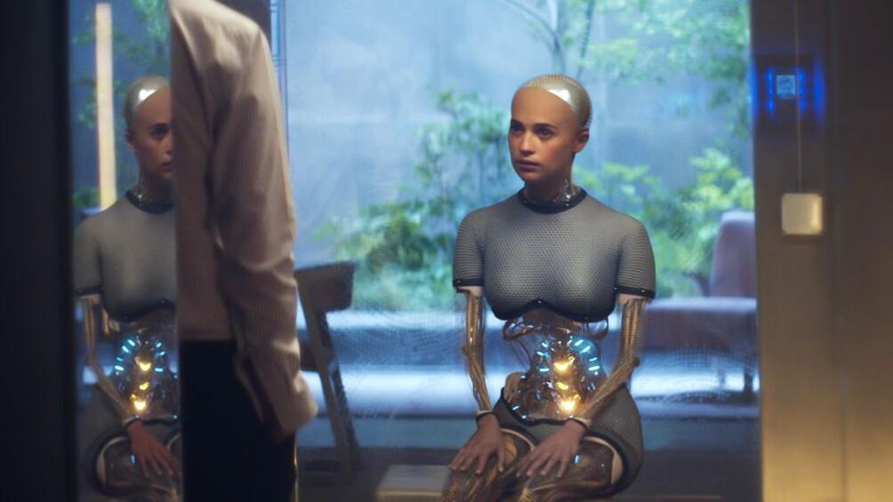 Die Roboterfrau Ava ist im Zentrum des Bildes zu sehen, sie befindet sich in einem Glaskasten.