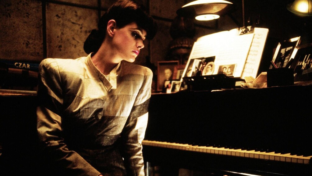Rachael sitzt vor einem Klavier, sie hält eine Zigarette in der Hand.