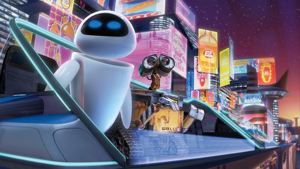 Die beiden Roboter Wall-E und Eve sind in einem nächtlichen Großstadtszenario mit vielen Leuchtreklamen abgebildet.