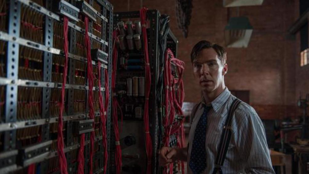 Auf dem Foto ist der Wissenschaftler Alan Turing neben einer großen Maschine abgebildet.