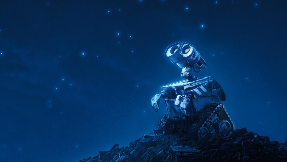 Der Roboter Wall-E steht auf einem Schrotthaufen und blickt in den dunklen Sternenhimmel.