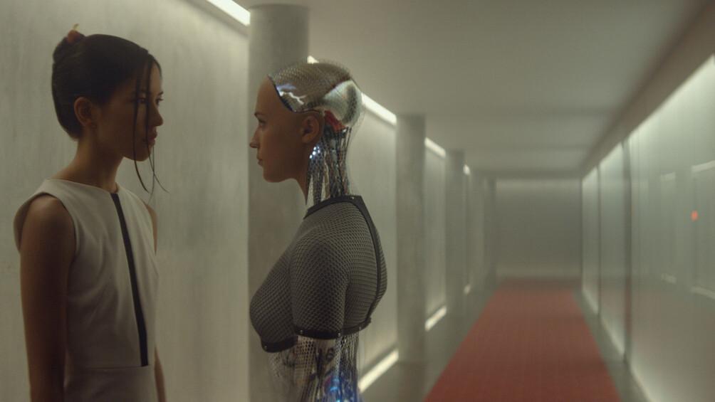 Die Roboter Kyoko und Ava stehen sich gegenüber und blicken sich an. Hinter ihnen befindet sich ein langer Flur.