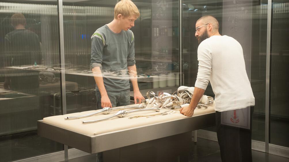 Nathan und Caleb stehen in einem Glaskasten um einen Tisch herum. Auf dem Tisch liegen verschiedene Teile eines Roboters.