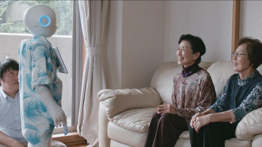 Der Roboter Pepper steht in einem Wohnzimmer, ihm gegenüber sitzen zwei Frauen.