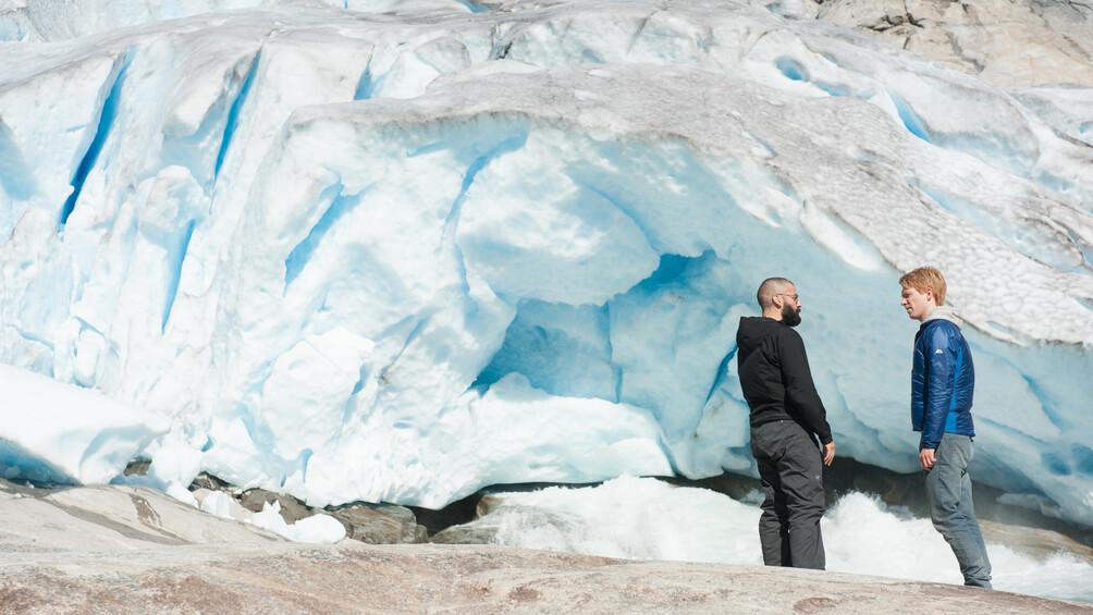 Nathan und Caleb stehen vor Gletschern, die blau zu leuchten scheinen.