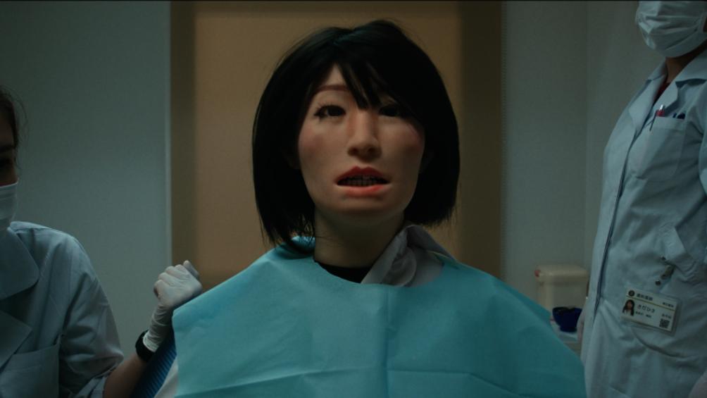 Eine Roboterfrau sitzt beim Zahnarzt, rechts und links von ihr befinden sich Ärzte.