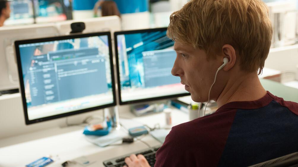 Caleb sitzt vor zwei großen Bildschirmen in einem modernen Büro, er blickt nach links.