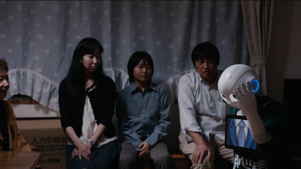 Vier Personen sitzen um den Roboter Pepper herum und sehen ihn an. Er fasst sich anden Kopf und blickt auf den Boden.