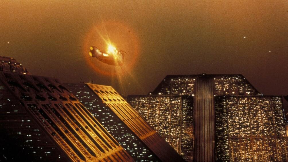Dächer einer Stadt sind dargestellt, es ist nachts, Lichter leuchten in den Fenstern, am Horizont sieht man ein Raumschiff.