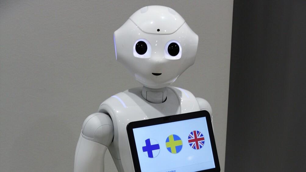 Ein Serviceroboter ist zu sehen, er trägt ein iPad vor sich, auf dem zwischen verschiedenen Sprachen ausgewählt werden kann.