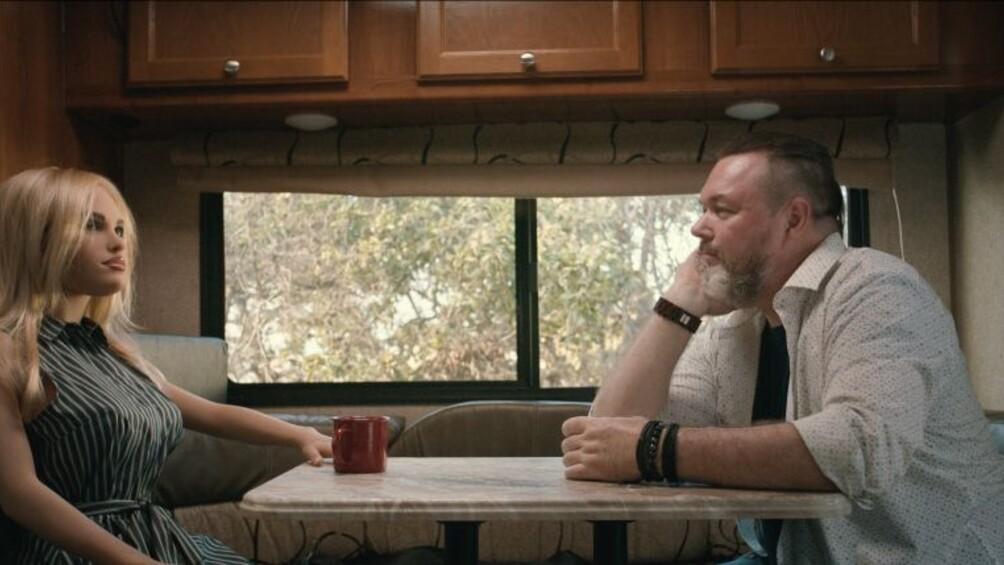 Die Roboterfrau Harmonie und ihr Besitzer Chuck sitzen sich in einem Wohnmobil gegenüber.