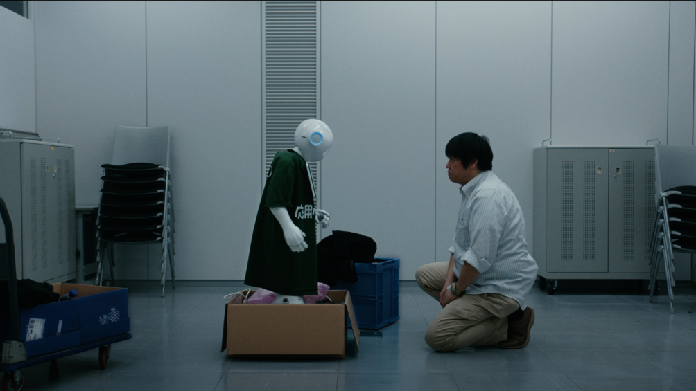 In einem Raum stehen sich ein Roboter und ein Mann gegenüber, sie blicken sich an.