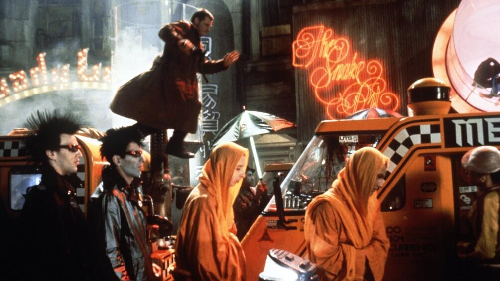 Eine düstere Straßenszenerie ist dargestellt, es ist nachts, im Vordergrund laufen vermummte Gestalten, im Hintergrund sieht man den Replikantenjäger Deckard.