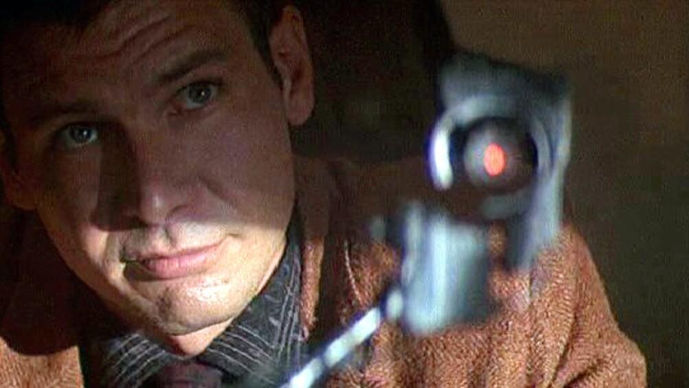 Der Replikantenjäger Deckard blickt nach oben, er scheint durch ein techinsches Gerät zu blicken.