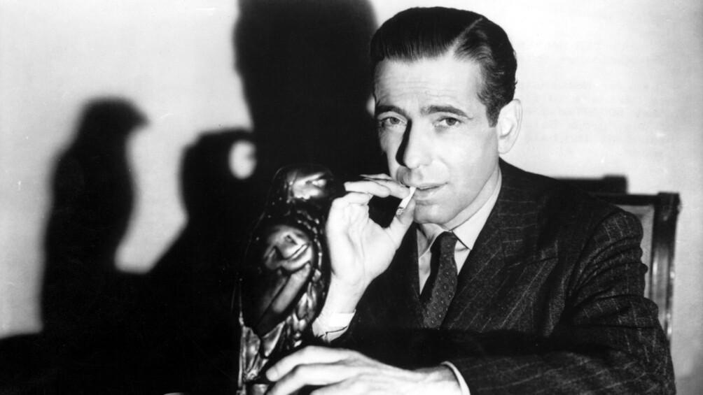 Auf der Fotografie ist Humphrey Bogart dargestellt. Er zieht an einer Zigarette und blickt direkt in die Kamera.