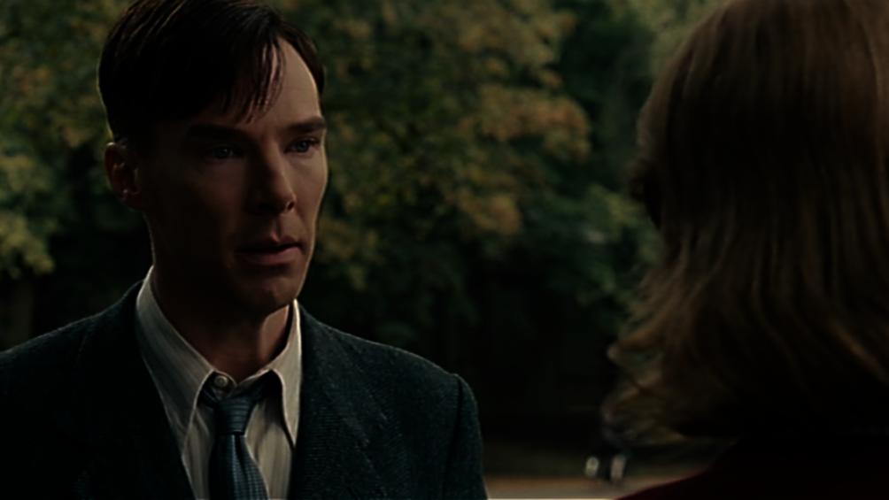 Auf dem Bild sieht man Alan Turing, wie er gerade mit Joan Clark redet.